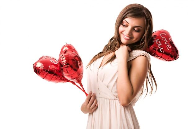 Junge schöne positive brünette frau im beige kleid stehend, rote herzförmige luftballons in den händen haltend und lächelnd