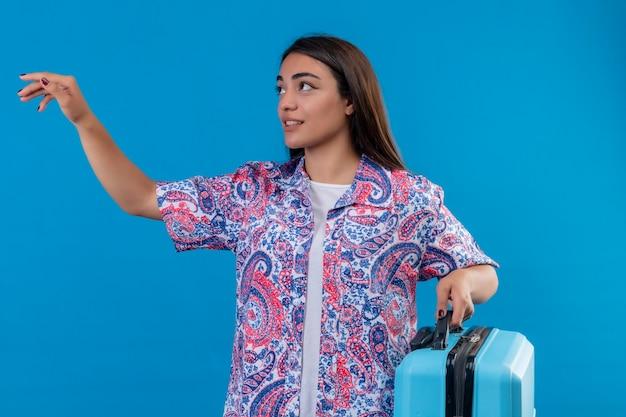 Junge schöne reisende frau, die blauen koffer hält, der beiseite gestikuliert mit der hand bittet, über blauem hintergrund stehend zu kommen