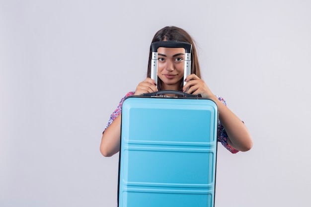 Junge schöne reisende frau, die blauen koffer hält, der durch den griff schlau über weiße wand schaut