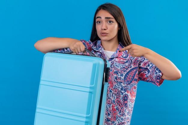 Junge schöne reisende frau, die blauen koffer hält, der mit dem finger darauf zeigt und verwirrt und überrascht über blauem hintergrund steht