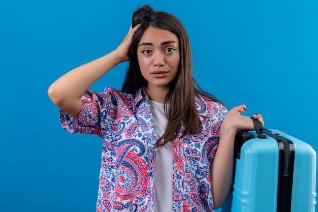 Junge schöne reisende frau, die blauen koffer hält, der mit hand auf kopf für fehler verwirrt schaut, erinnern fehler vergessen schlechtes gedächtniskonzept über isoliertem blauem hintergrund