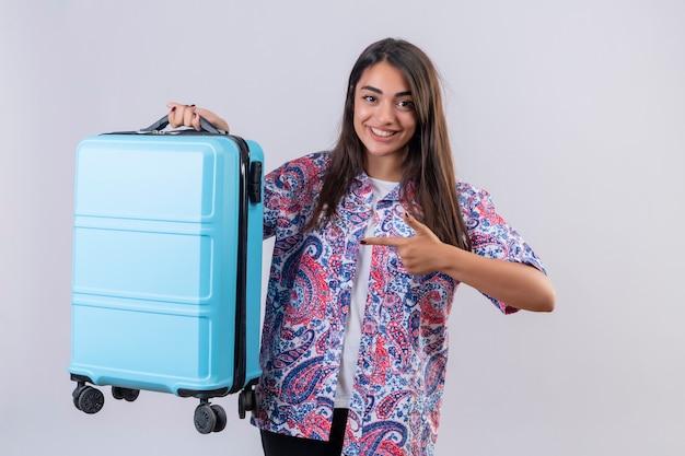Junge schöne reisende frau, die blauen koffer hält, der mit zeigefinger darauf zeigt, der fröhlich über weißem hintergrund stehend lächelt