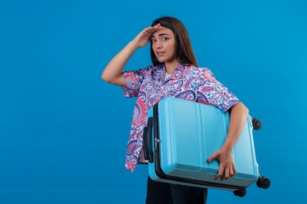 Junge schöne reisende frau, die blauen koffer hält, der müde steht mit hand auf kopf über blauem hintergrund steht