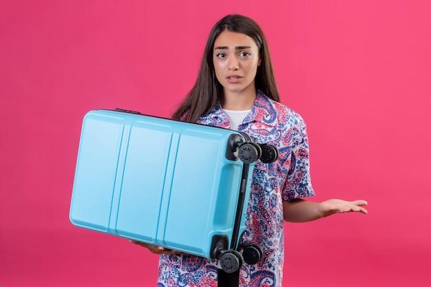 Junge schöne reisende frau, die koffer, der schultern zuckt, die zweifel mit verwirrendem gesichtsausdruck über isolierter rosa wand halten