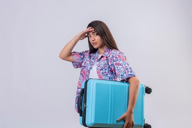 Junge schöne reisende frau, die koffer hält, der müden berührenden kopf steht, der über lokalisiertem weißem hintergrund steht