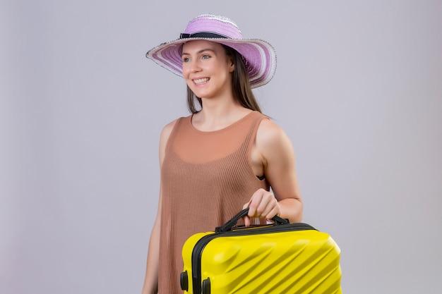 Junge schöne reisende frau im sommerhut, der gelben koffer hält, der mit glücklichem gesicht über weißer wand lächelt