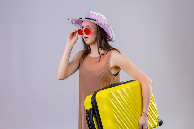 Junge schöne reisende frau im sommerhut, die rote sonnenbrille hält, die gelben koffer hält, der überrascht und enttäuscht über weißem hintergrund steht