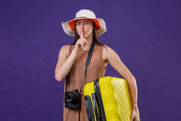 Junge schöne reisende frau im sommerhut mit gelbem koffer und kamera, die stille geste mit dem finger auf den lippen macht, die über lila hintergrund stehen