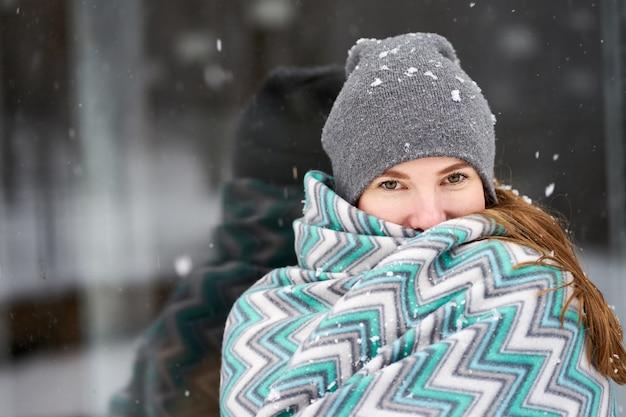 Junge schöne rothaarige frau bedeckt mit blauer decke, die ihr gesicht im schneefall versteckt
