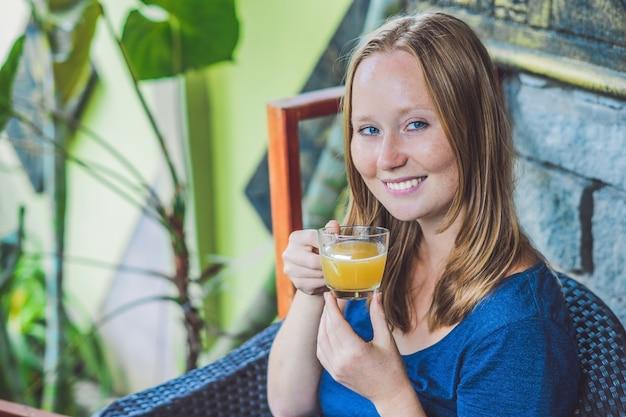 Junge schöne rothaarige frau, die in einem café sitzt, das einen köstlichen morgen-ingwertee in einem café trinkt