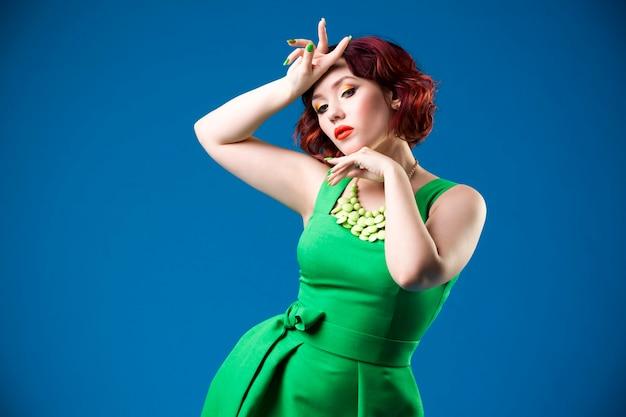 Junge schöne rothaarige kaukasische frau im grünen kleid, das im studio aufwirft