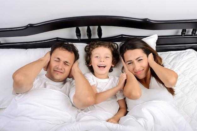 Junge schöne schlafende familie mit dem kleinen sohn.