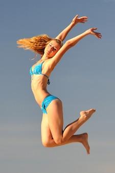 Junge schöne schlanke frau im blauen bikini, der über sand mit regenschirm springt