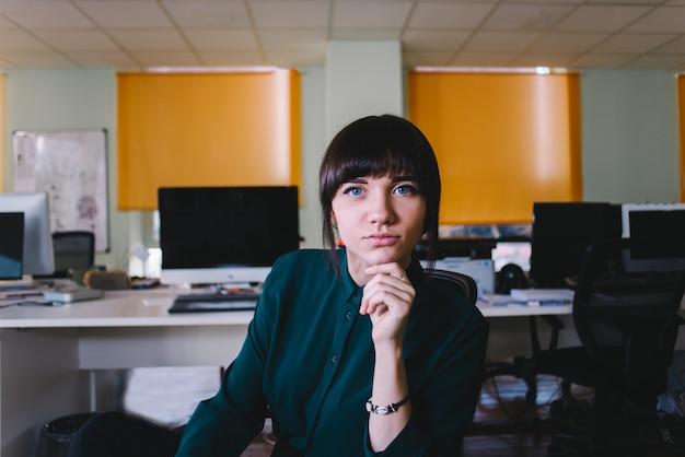 Junge schöne schöne frau des arbeiters, die in einem modernen büro sitzt und die kamera betrachtet. büroleben