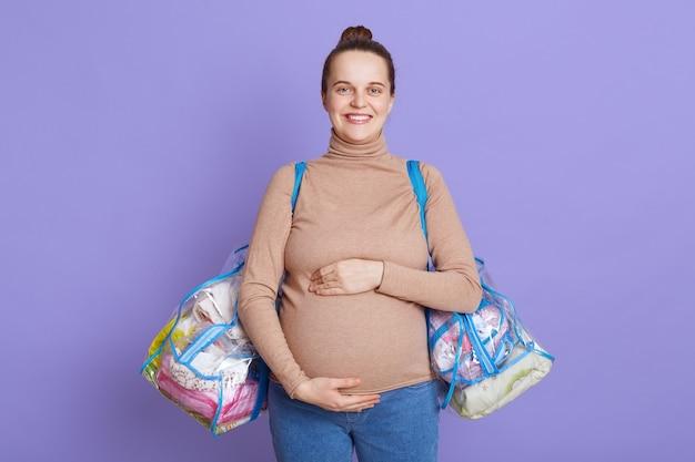 Junge schöne schwangere frau, die isoliert über lila wand steht, ihren bauch berührend, taschen mit sachen für mutterschaftshaus haltend.