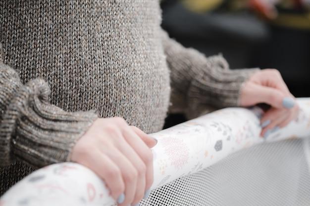 Junge schöne schwangere frau, die kinderwagen oder kinderwagen für neugeborene wählt.