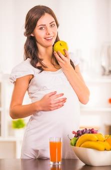 Junge schöne schwangere frau, die nahrung zubereitet.