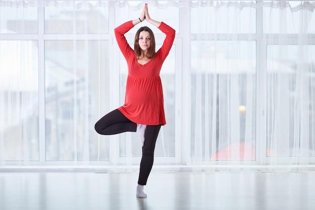 Junge schöne schwangere frau, die yoga asana vrikshasana tut