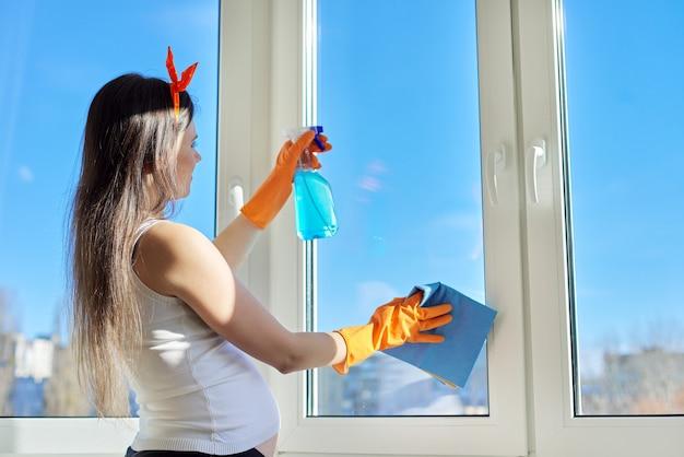Junge schöne schwangere frau in den handschuhen mit lappen des waschmittels, das hauptreinigung tut