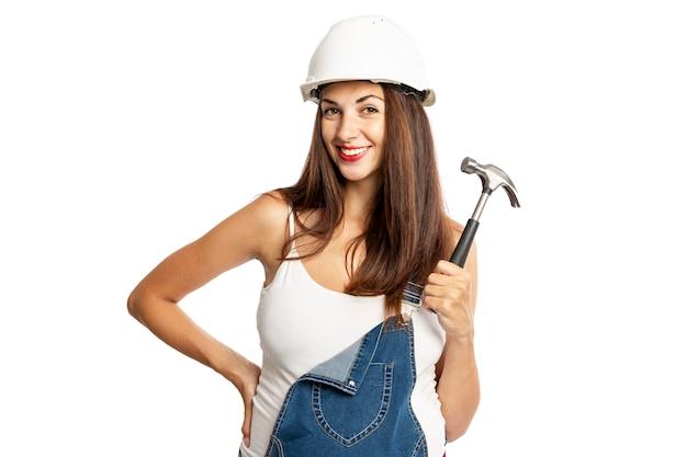 Junge schöne schwangere frau in einem sturzhelm mit einem hammer in ihrer hand. isoliert auf weißem hintergrund