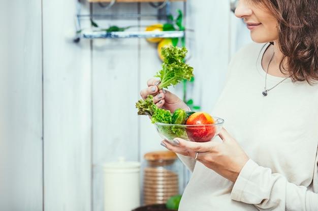 Junge schöne schwangere frau mit gesunden vegetarischen mahlzeiten in der küche zu hause