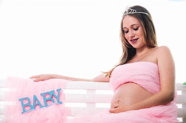 Junge schöne schwangere frau wirft auf. sie sah ihren bauch an