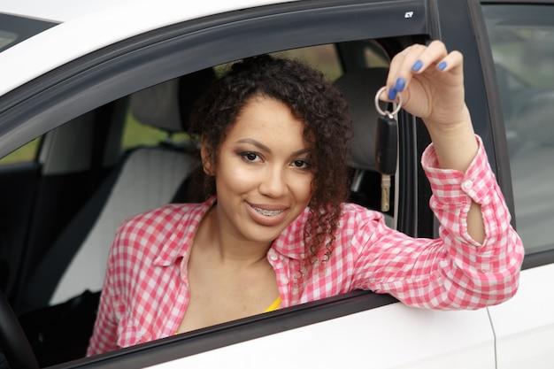 Junge schöne schwarze fahrerin mit autoschlüsseln, die ihr neues auto fahren driving