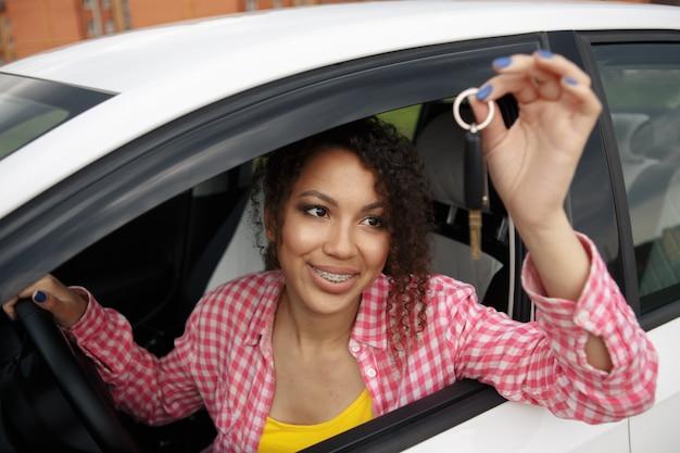 Junge schöne schwarze teenager-fahrerin, die autoschlüssel hält, die ihr neues auto fährt
