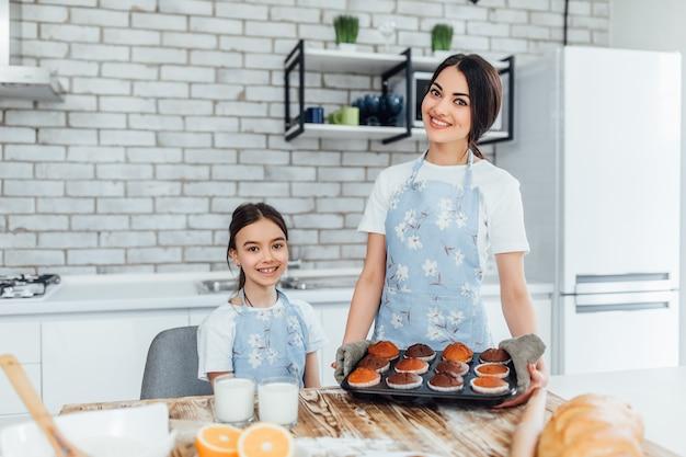 Junge schöne schwestern kochen eine menge cupcakes