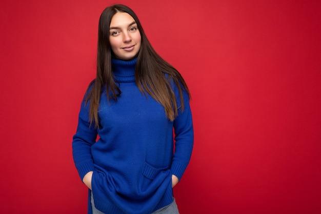 Junge schöne selbstbewusste brünette frau mit aufrichtigen emotionen isoliert auf der hintergrundwand mit kopierraum, die einen lässigen, trendigen blauen pullover trägt. positives konzept