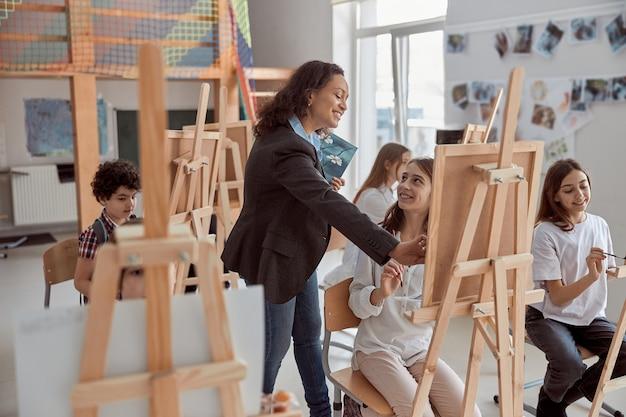 Junge schöne selbstbewusste lehrerin hilft einem kind, auf eine gruppenstunde in einem weißen, modernen, minimalistischen klassenzimmer zurückzugreifen