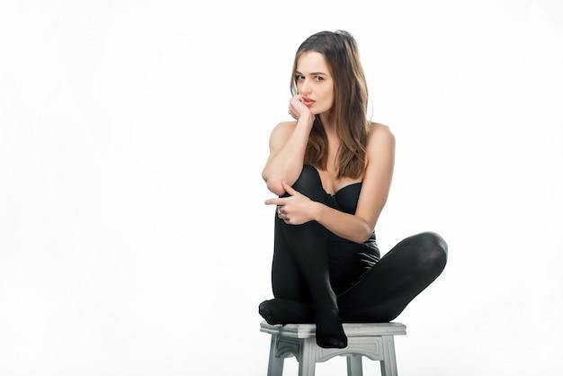 Junge schöne sexy frau, die das sitzen in der schwarzen wäsche und in den strumpfhosen auf einem stuhl aufwirft