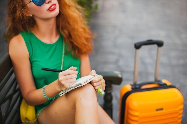 Junge schöne sexy frau, hipster-outfit, rote haare, reisender, grünes oberteil, orangefarbener koffer, notizen machen, reisetagebuch