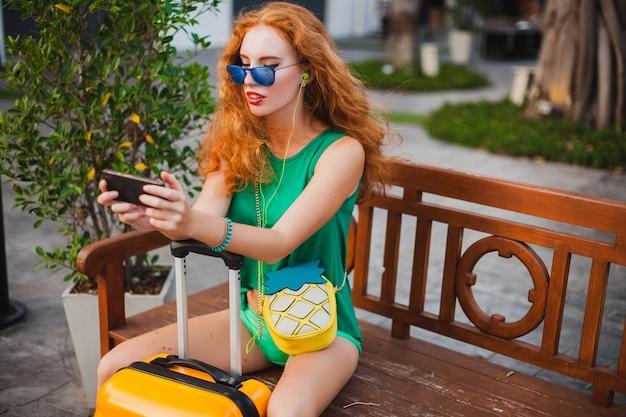 Junge schöne sexy frau, hipster-stil, rote haare, reisender, grünes oberteil, shorts, orangefarbener koffer, sommerferien, reisen, sitzen, warten, halten von smartphone, sonnenbrille, musik hören, kopfhörer