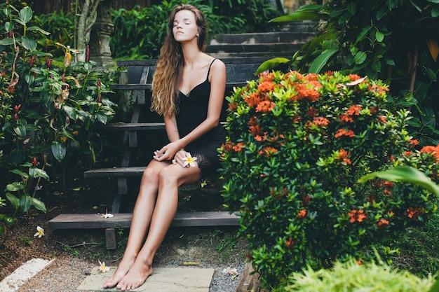 Junge schöne sexy frau im tropischen garten, sommerferien in thailand, schlanker dünner gebräunter körper, kleines schwarzes kleid mit spitze, natürlicher blick, sinnlich, entspannt,
