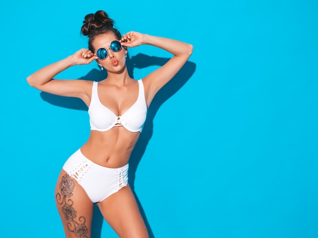 Junge schöne sexy frau mit ghulfrisur. modisches mädchen im weißen badeanzug des zufälligen sommers in der sonnenbrille heißes modell lokalisiert auf blau macht entengesicht