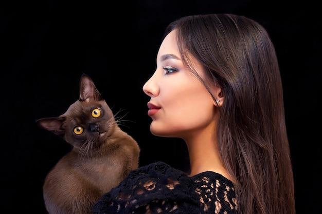 Junge schöne sexy frau mit hellem make-up mit einer katze in ihren händen auf einem schwarzen hintergrund