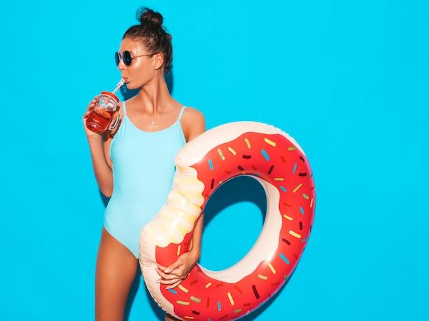 Junge schöne sexy lächelnde hippie-frau in der sonnenbrille mädchen im badeanzug der sommerbadebekleidung mit aufblasbarer matratze des donut lilo positive frau, die verrückt geht aufstellung nahe blauer wand