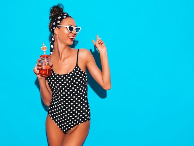 Junge schöne sexy lächelnde hippie-frau in der sonnenbrille mädchen im badeanzug der sommererbsen-badebekleidung aufstellung nahe der blauen wand, trinkendes neues cocktail smoozy getränk zeigt friedenszeichen