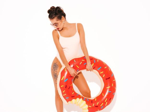 Junge schöne sexy lächelnde hippie-frau mit den roten lippen in der sonnenbrille mit aufblasbarer matratze des donut lilo