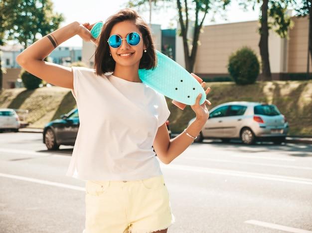 Junge schöne sexy lächelnde hipster-frau in der sonnenbrille. trendiges mädchen im sommer-t-shirt und in den kurzen hosen. positive frau mit blauem penny-skateboard, das auf dem straßenhintergrund aufwirft