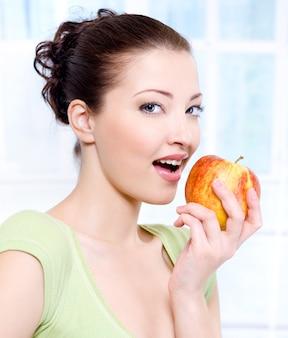 Junge schöne sinnlichkeitsfrau, die apfel isst