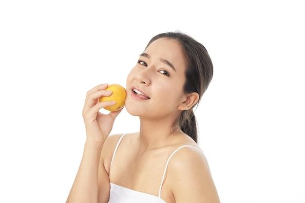 Junge schöne spa-frau mit orange in ihrer hand lokalisiert auf weißem hintergrund
