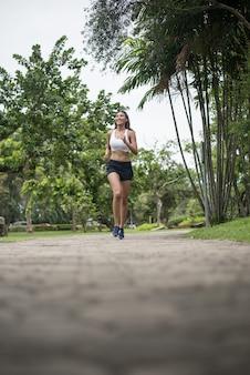 Junge schöne sportfrau, die am park läuft. gesundheits- und sportkonzept.