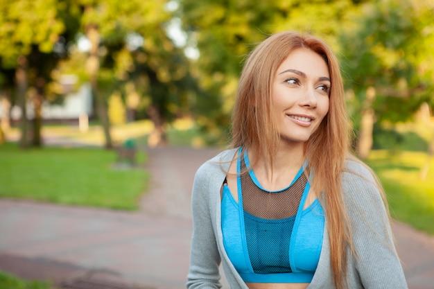 Junge schöne sportlerin, die in den park läuft