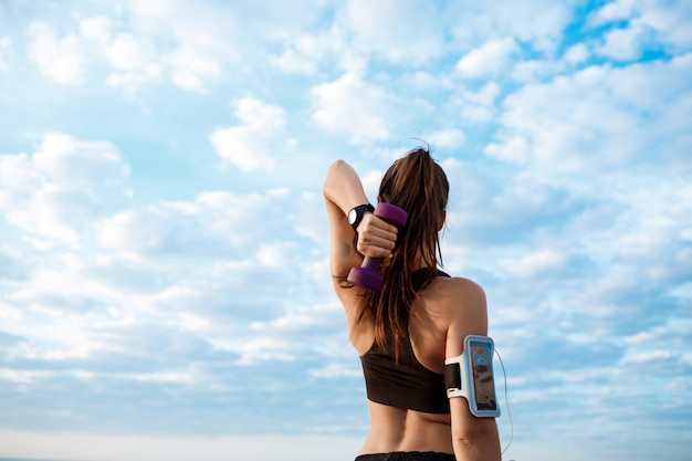 Junge schöne sportliche mädchenausbildung bei sonnenaufgang über dem meer.