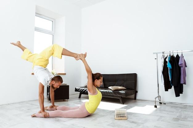 Junge schöne sportliche paar trainingspartner yoga asanas zu hause.