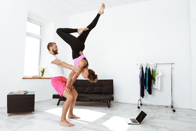 Junge schöne sportliche paare, die yoga-asanas zu hause trainieren.