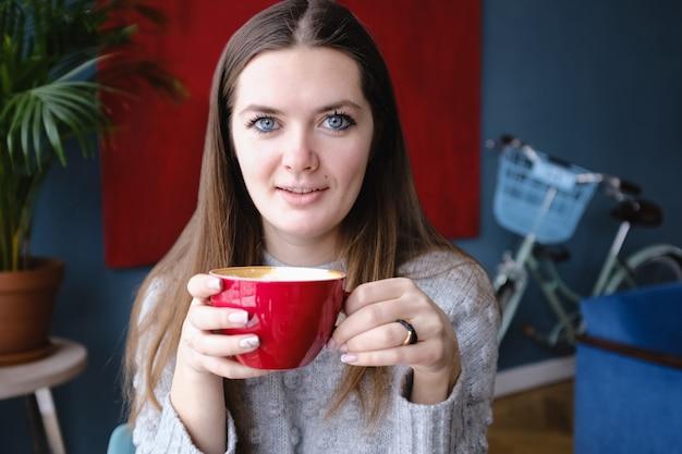 Junge schöne stilvolle frau, die in einem café, eine schale cappuccino halten sitzt und betrachten die kamera und genießen, stadtstraße, romantisches abendessen, sonnig. mädchen, das kaffee trinkt. frühstück. kaffeepause. wärmt