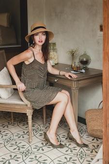 Junge schöne stilvolle frau im resort-hotelzimmer, sitzend am tisch, tragendes kleid, safari-stil, strohhut, lächelnd, glücklich, sommerferien, böhmisches outfit